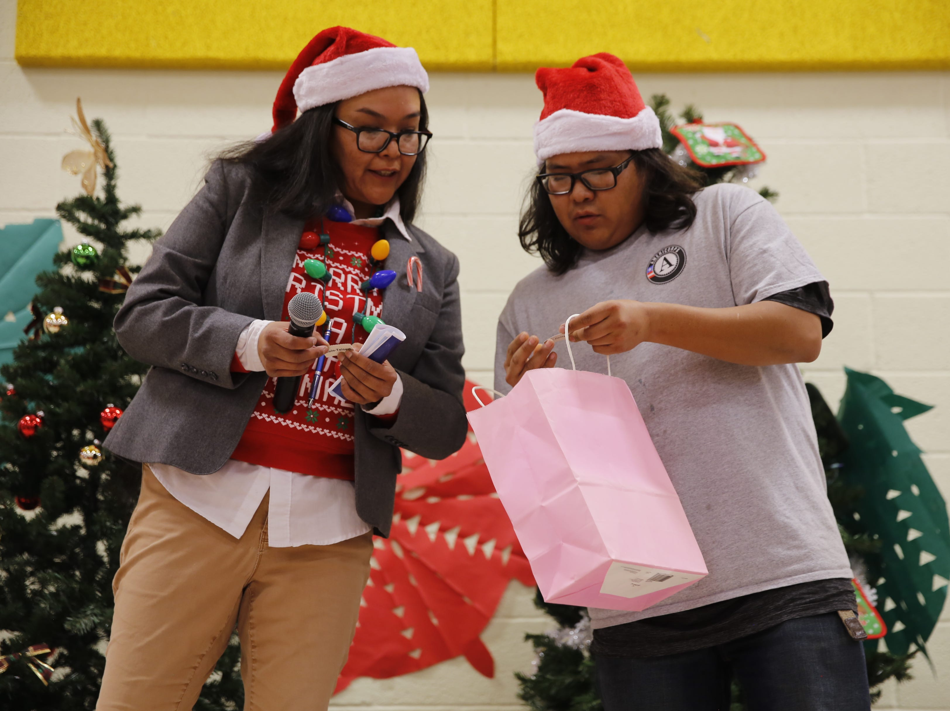 Trini King, left, and Arnold Keeswood check ticket numbers for a raffle during the family winter conference organized by Restoring and Celebrating Family Wellness on Wednesday at the Shiprock Youth Complex in Shiprock.
