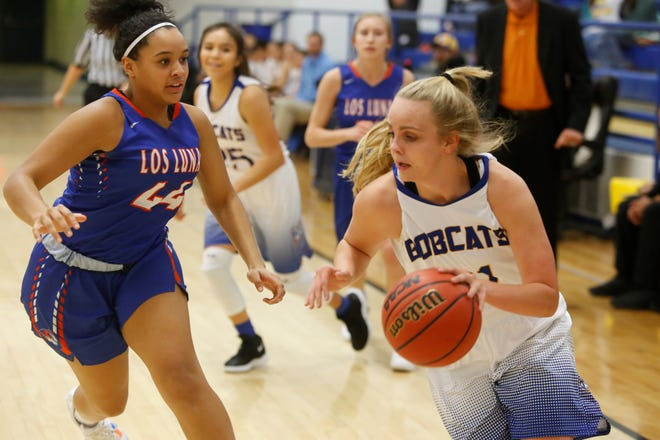 Bloomfield's Halle Payne drives toward the basket against Feleena Gabaldon of Los Lunas during Tuesday's game at Bobcat Gym.