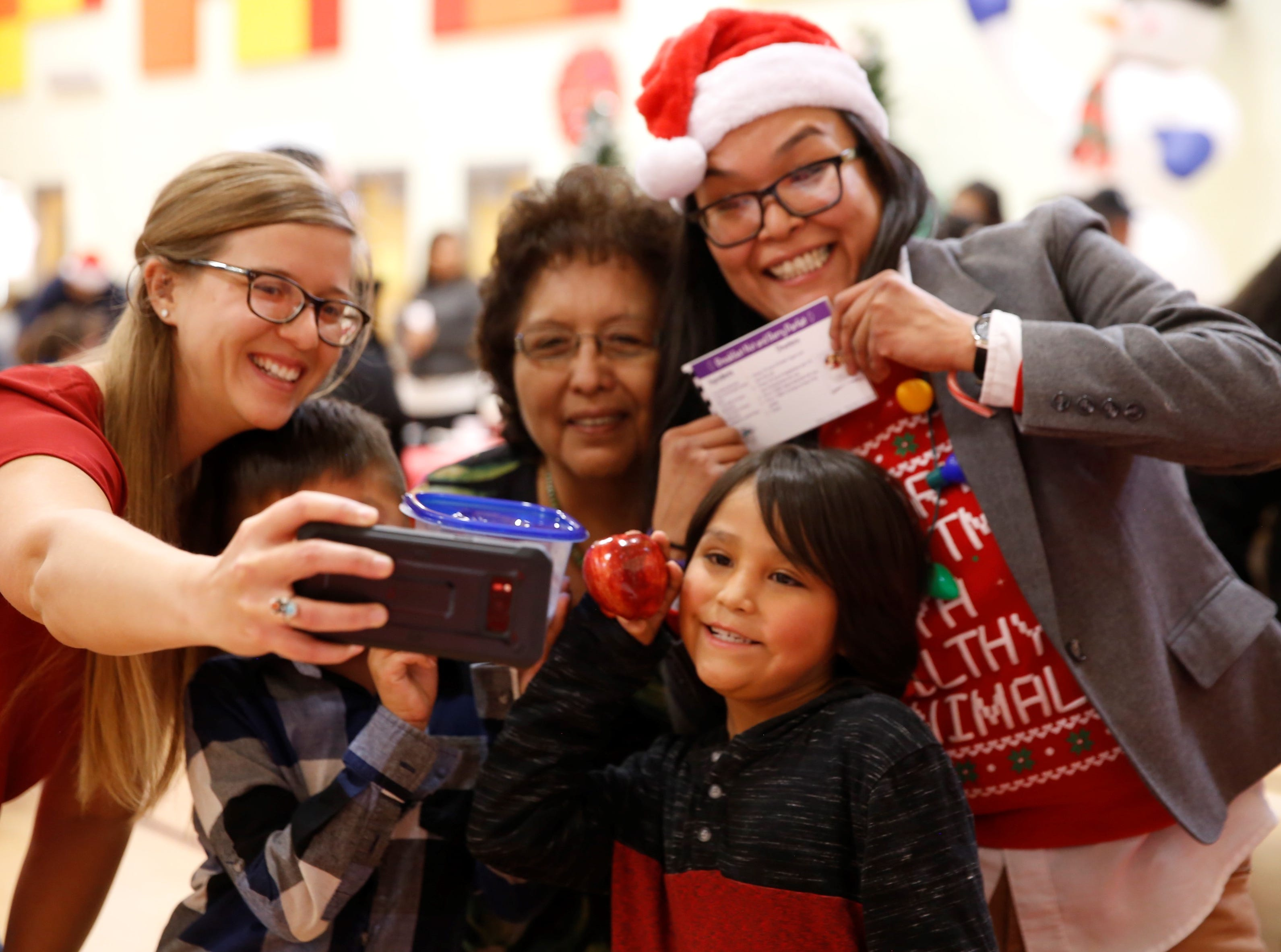 Katie Brown uses a smartphone to take a group selfie as part of an activity at the family winter conference on Wednesday at the Shiprock Youth Complex in Shiprock.