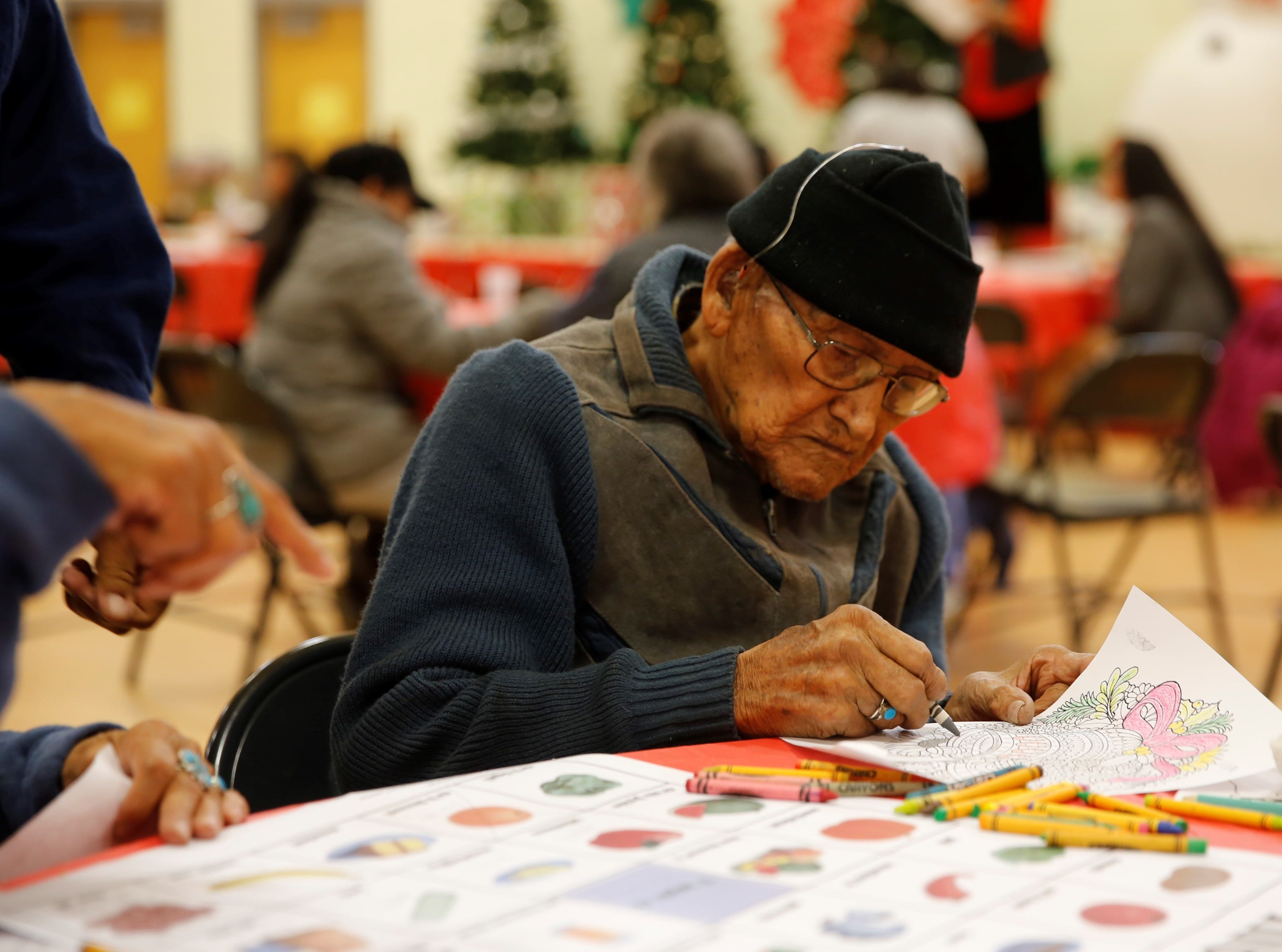 Howard Lee colors a holiday design during the family winter conference organized by Restoring and Celebrating Family Wellness at the Shiprock Youth Complex on Wednesday in Shiprock.