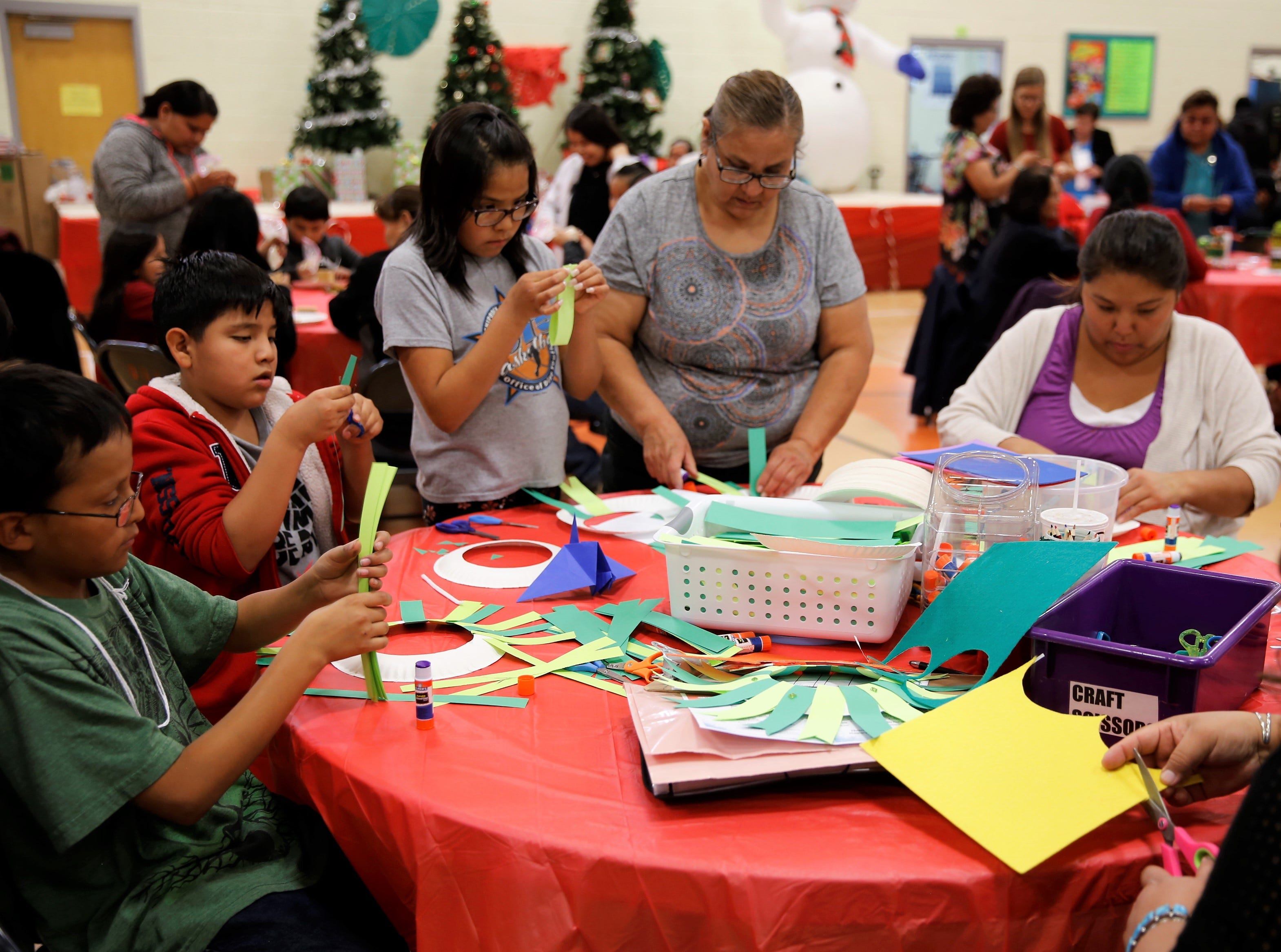 Participants make Christmas wreaths from paper plates and green paper during the family winter conference on Wednesday at the Shiprock Youth Complex in Shiprock.