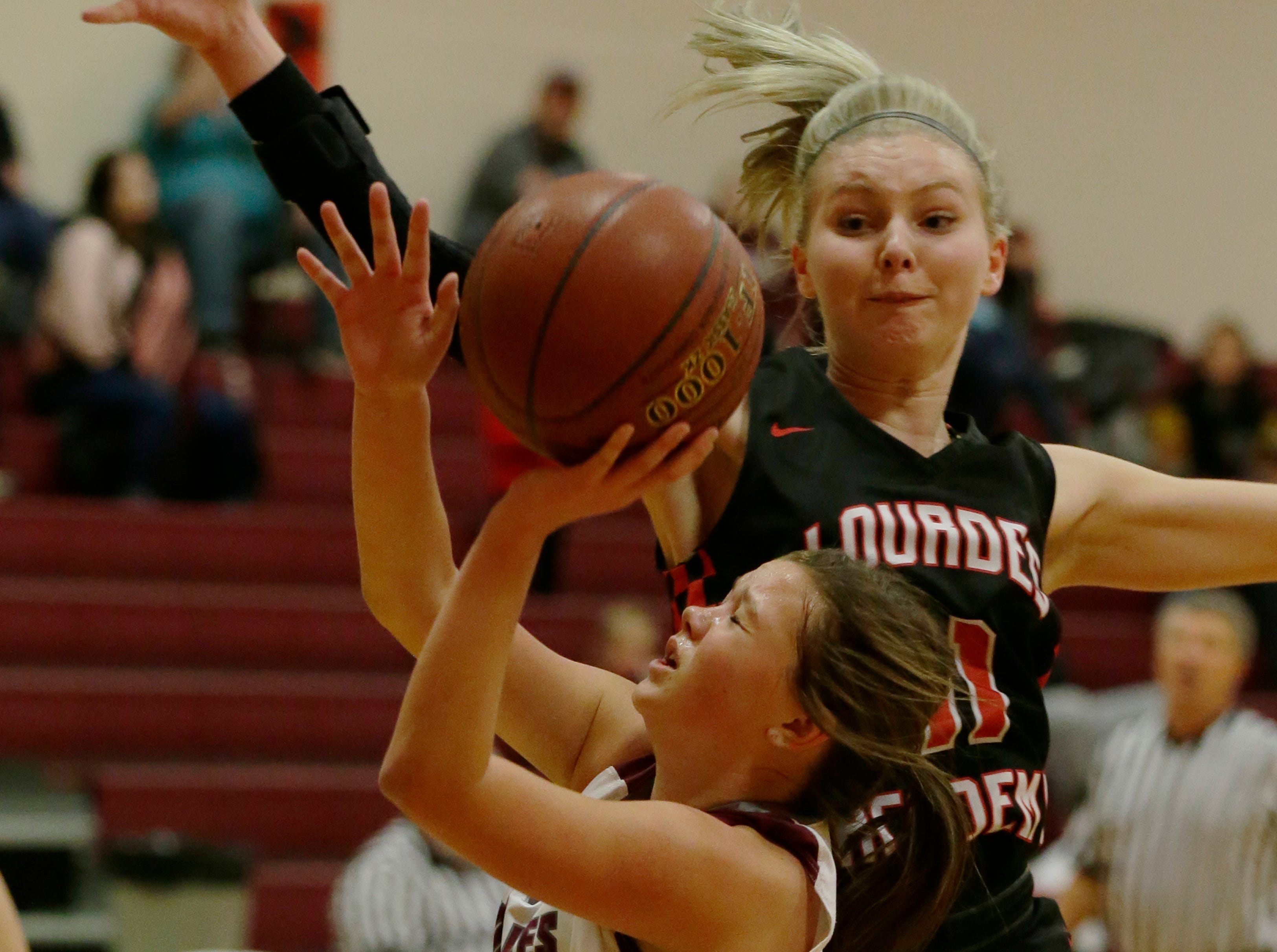 Lourdes Academy's Alexis Rolph gets ready to block Winneconne's Claire Gentry shot.  Winneconne Wolves played Lourdes Academy Knights, Tuesday, Dec. 11, 2018.  Winneconne won 56 - 44.