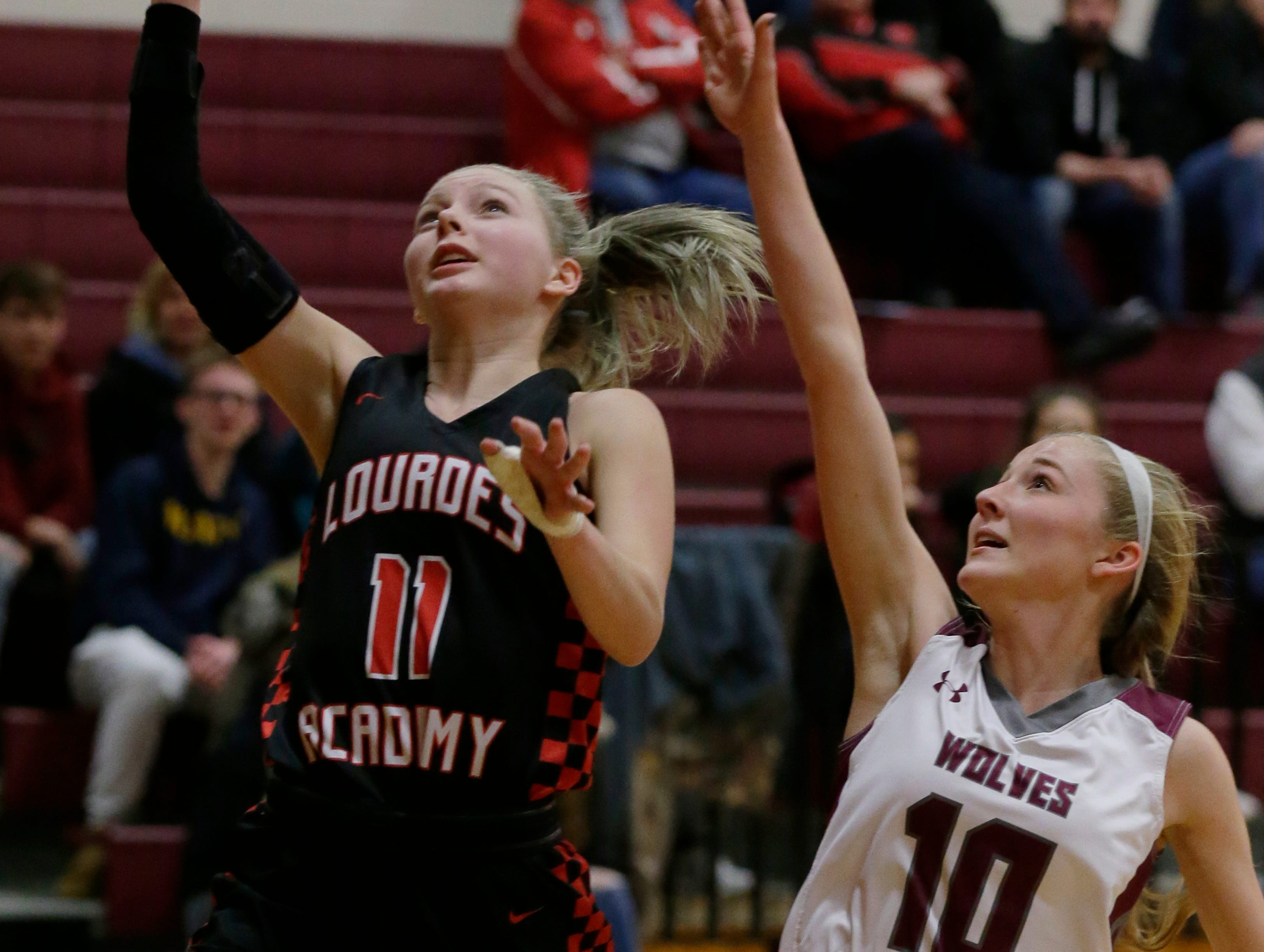 Lourdes Academy's Alexis Rolph goes in for a layup past Winneconne's Emily Heyroth.  Winneconne Wolves played Lourdes Academy Knights, Tuesday, Dec. 11, 2018. Winneconne won 56 - 44.