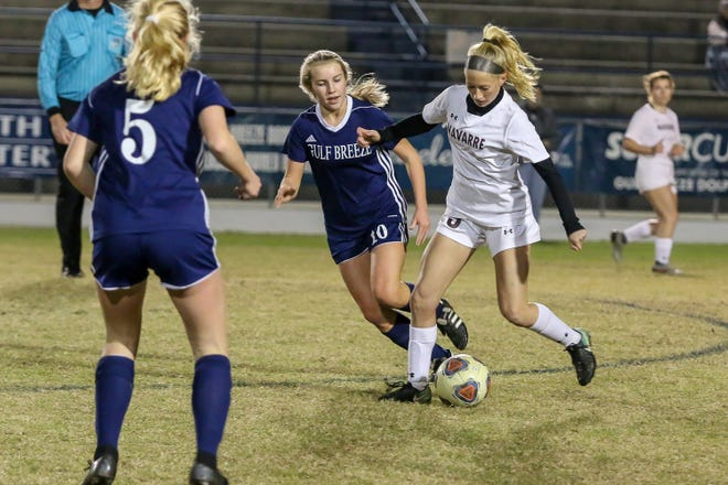 Navarre's Hailey Bastian (23) looks for an open lane to pass the ball through between Gulf Breeze's Morgan Williams (10) and Delaney Williams (5) during the game at Gulf Breeze High School on Tuesday, December 11, 2018.