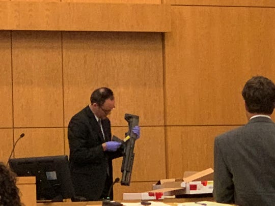 Florida Department of Law Enforcement crime lab analyst William Black holds the 12-gauge shotgun used by James Greenwood in the Nov. 21, 2014, shooting of Al Jones during Greenwood's trial on Wednesday.