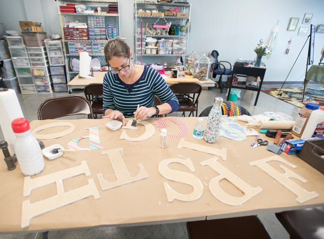 Manager Sharon Posey makes decoupage letters at the Maker's Loft on Pine Forest Road in Pensacola on Wednesday, December 12, 2018.