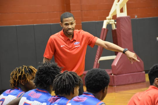 Pine Forest boys coach Ty McCants talks to his team during the Eagles' 69-50 victory Tuesday against Tate.