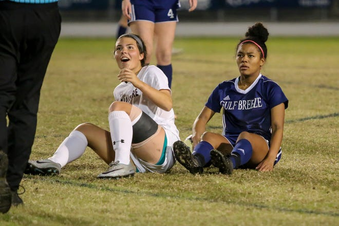 Gulf Breeze's Mya Swinton and Navarre's Anakah Madril look up in amazement as the official makes a call following the two colliding in the game at Gulf Breeze High School on Tuesday, December 11, 2018.