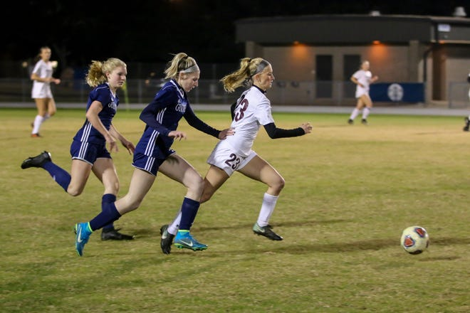 Navarre's Hailey Bastian (23) sprints up the field with the ball as Gulf Breeze's Delaney Williams, left, and Riley Cassidy chase after her during the game at Gulf Breeze High School on Tuesday, December 11, 2018.