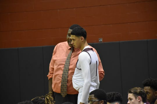 Tate boys coach Clyde Abney talks to his senior star Yaseen Moftaqir after he fouled out in the fourth quarter of the Aggies loss Tuesday against Pine Forest