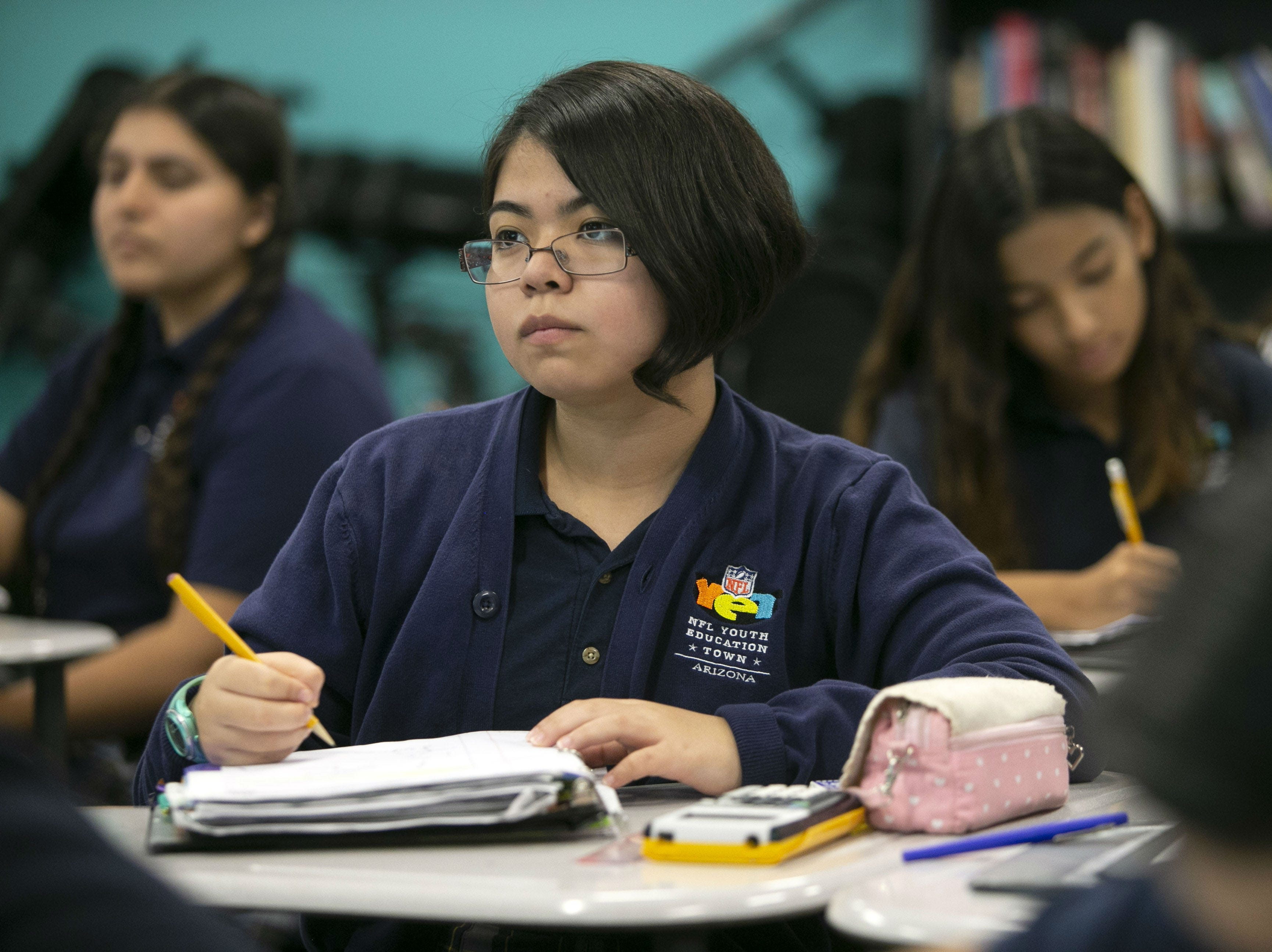 Isabel Huerta, 16, listens during a physics class at the NFL YET College Prep Academy, a seventh-12th grade charter school in south Phoenix, on Nov. 5, 2018.