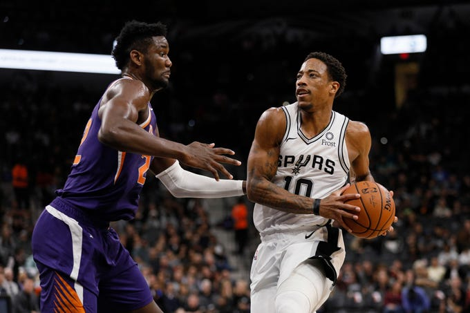 Dec 11, 2018; San Antonio, TX, USA; San Antonio Spurs shooting guard DeMar DeRozan (10) drives to the basket as Phoenix Suns center Deandre Ayton (left) defends during the first half at AT&T Center. Mandatory Credit: Soobum Im-USA TODAY Sports