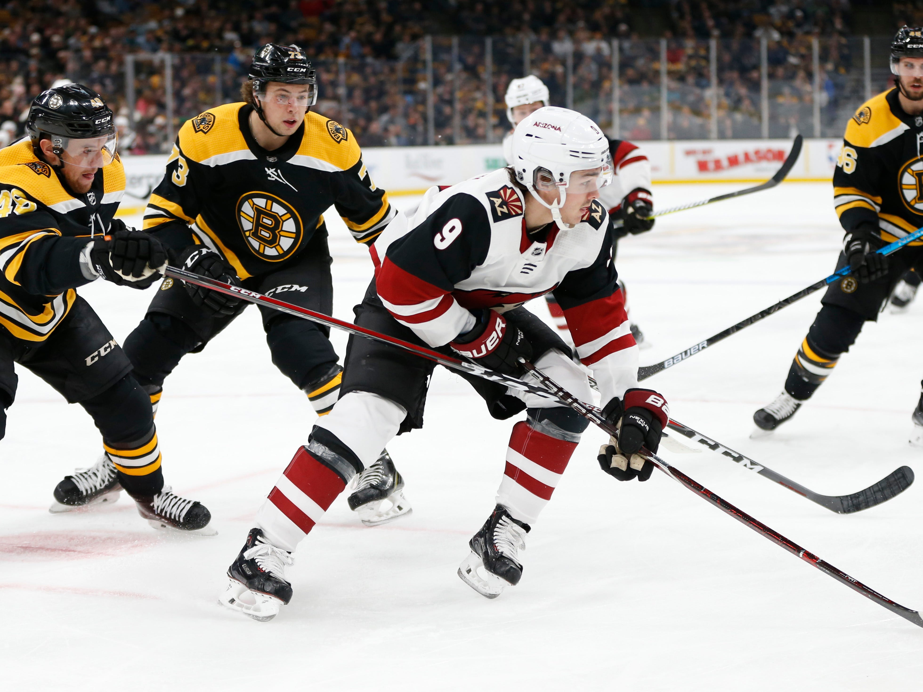 Dec 11, 2018; Boston, MA, USA; Arizona Coyotes center Clayton Keller (9) is defended by Boston Bruins defenseman Matt Grzelcyk (48) and defenseman Charlie McAvoy (73) during the first period at TD Garden. Mandatory Credit: Greg M. Cooper-USA TODAY Sports