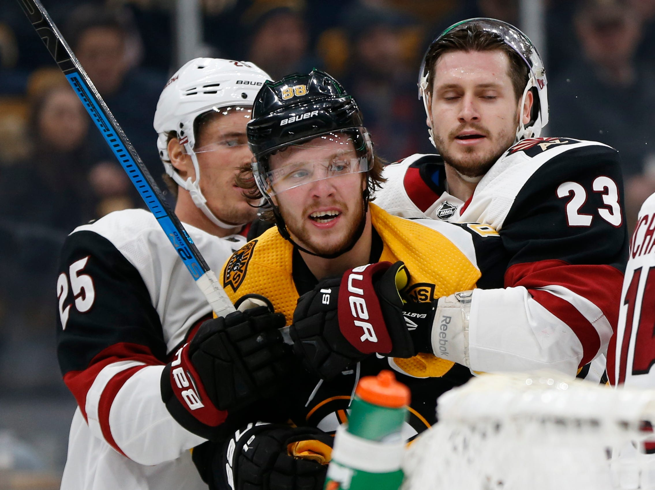 Dec 11, 2018; Boston, MA, USA; Arizona Coyotes center Nick Cousins (25) and defenseman Oliver Ekman-Larsson (23) restrain Boston Bruins right wing David Pastrnak (88) during the second period at TD Garden. Mandatory Credit: Greg M. Cooper-USA TODAY Sports