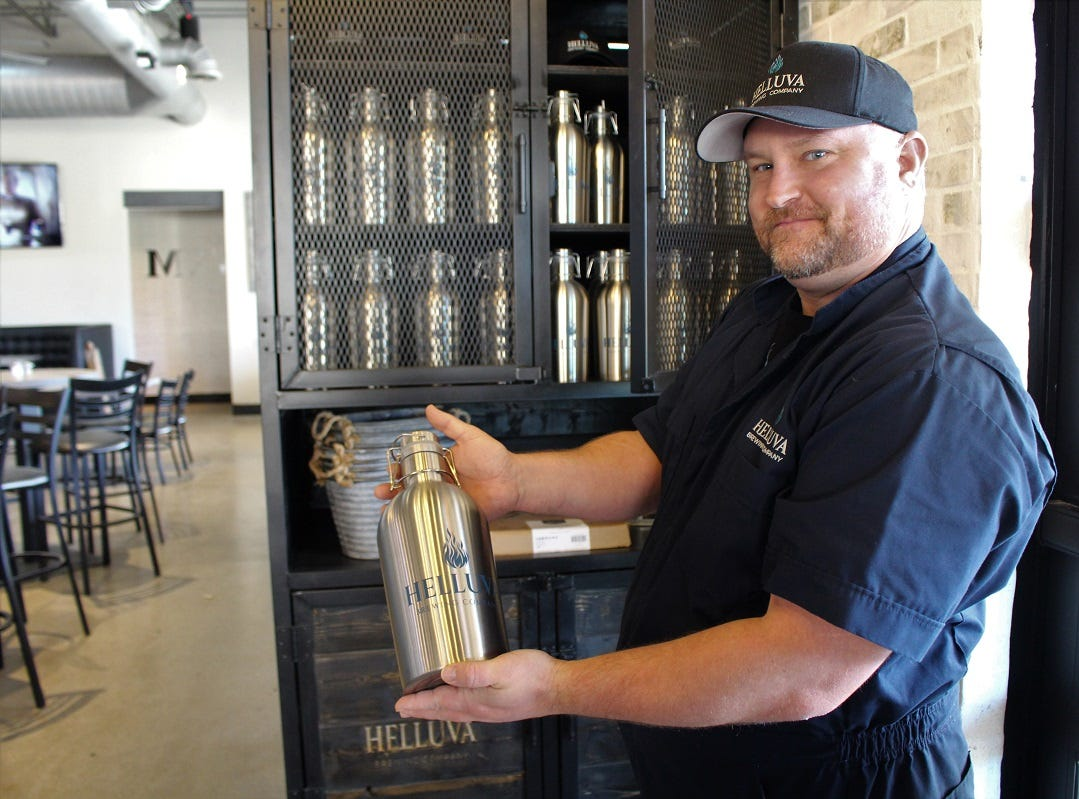 Co-owner Shawn Shepard of Helluva Brewing Company in Chandler shows off the breweries metal growlers.