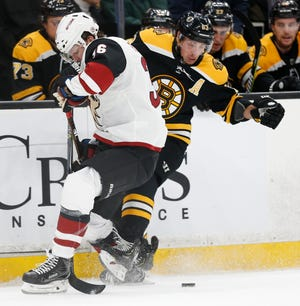 Dec 11, 2018; Boston, MA, USA; Arizona Coyotes right wing Christian Fischer (36) gets wrapped up with Boston Bruins left wing Brad Marchand (63) during the third period at TD Garden. Mandatory Credit: Greg M. Cooper-USA TODAY Sports