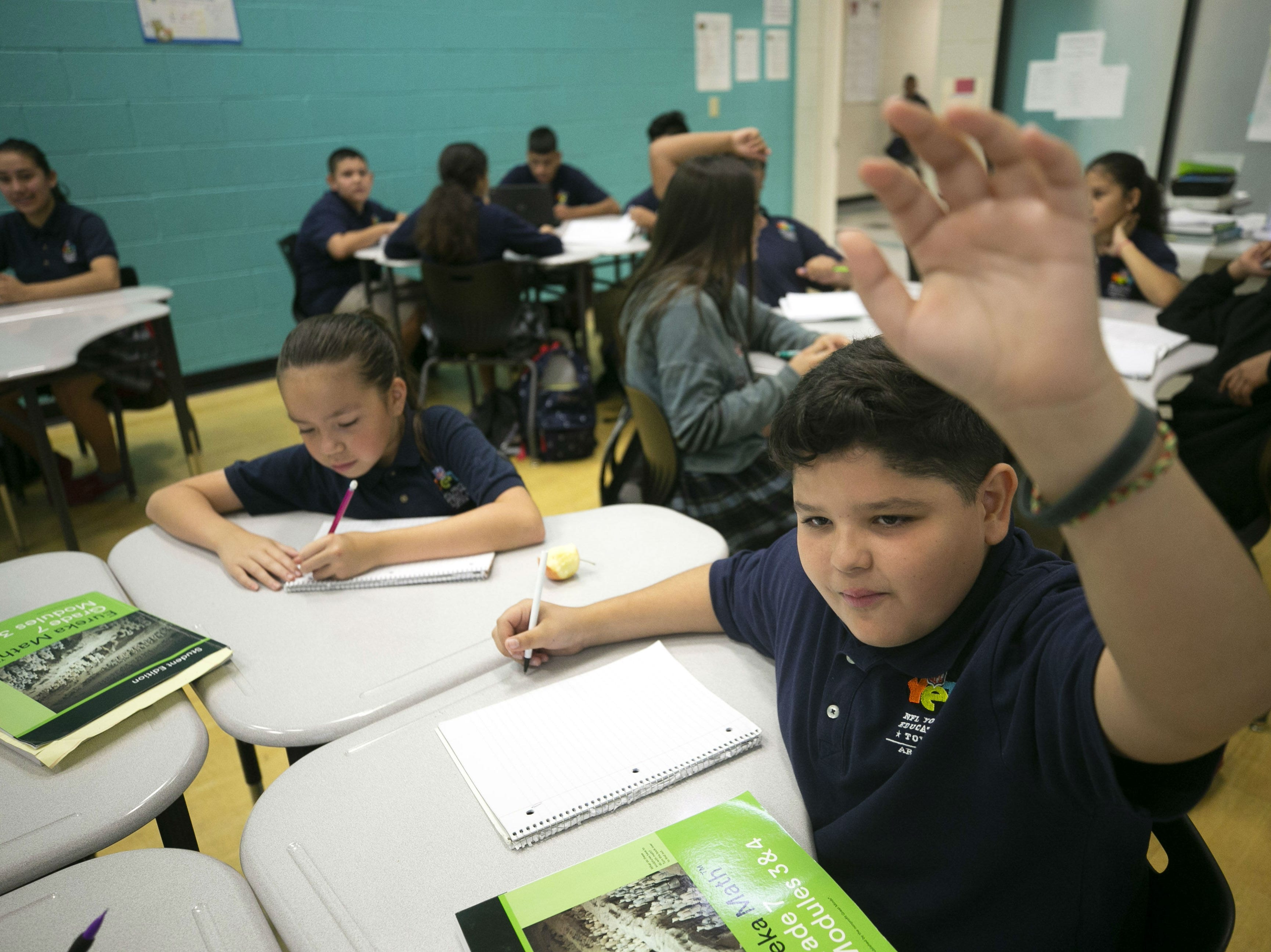 Israel Lopez Ramirez, 12, raises his hand in a seventh grade math class at the NFL YET College Prep Academy, a seventh-12th grade charter school in south Phoenix, on Nov. 5, 2018.