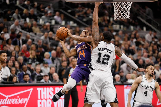 Dec 11, 2018; San Antonio, TX, USA; Phoenix Suns point guard De'Anthony Melton (14) shoots the ball under pressure from San Antonio Spurs power forward LaMarcus Aldridge (12) during the second half at AT&T Center. Mandatory Credit: Soobum Im-USA TODAY Sports