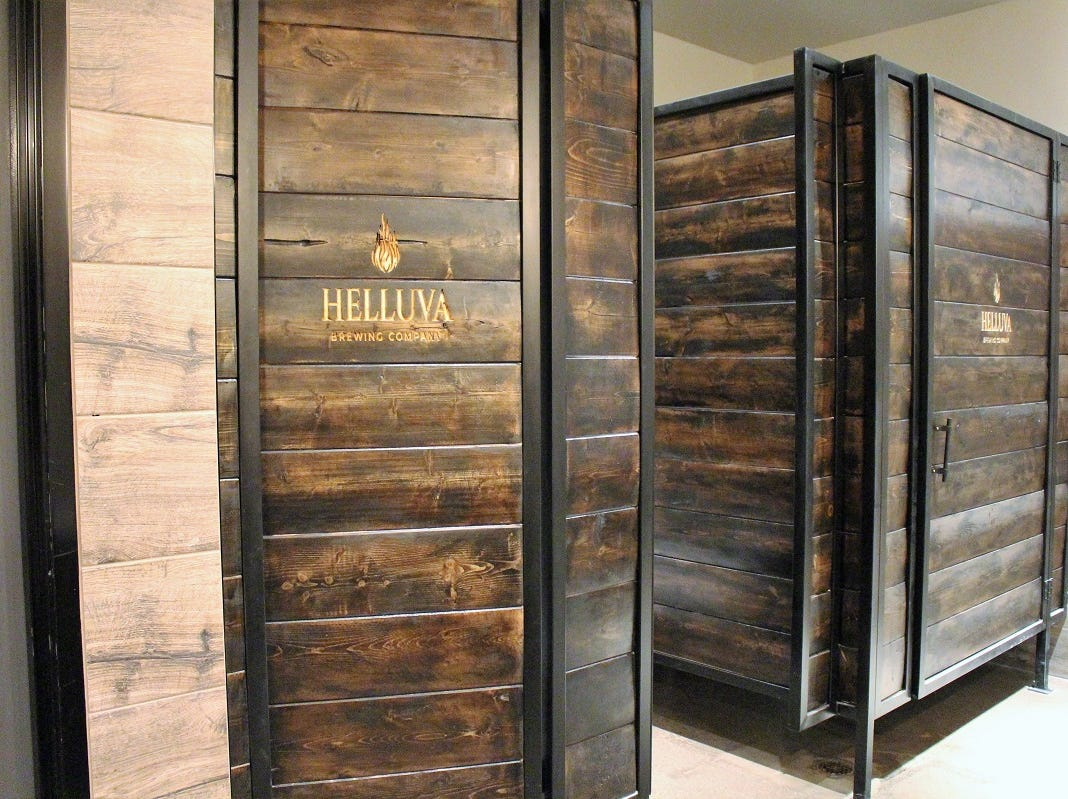 The bathrooms at Helluva Brewing Company in Chandler have custom engraved wooden stalls.