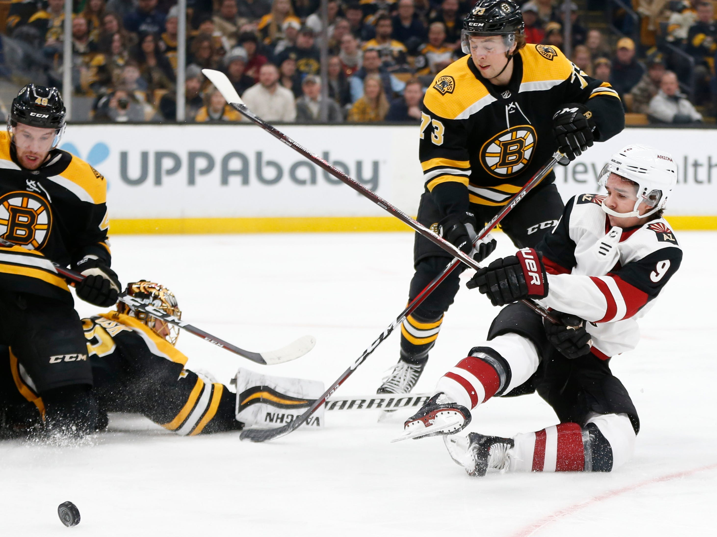 Dec 11, 2018; Boston, MA, USA; Arizona Coyotes center Clayton Keller (9) shoots towards Boston Bruins goaltender Tuukka Rask (40) while defended by defenseman Charlie McAvoy (73) during the first period at TD Garden. Mandatory Credit: Greg M. Cooper-USA TODAY Sports