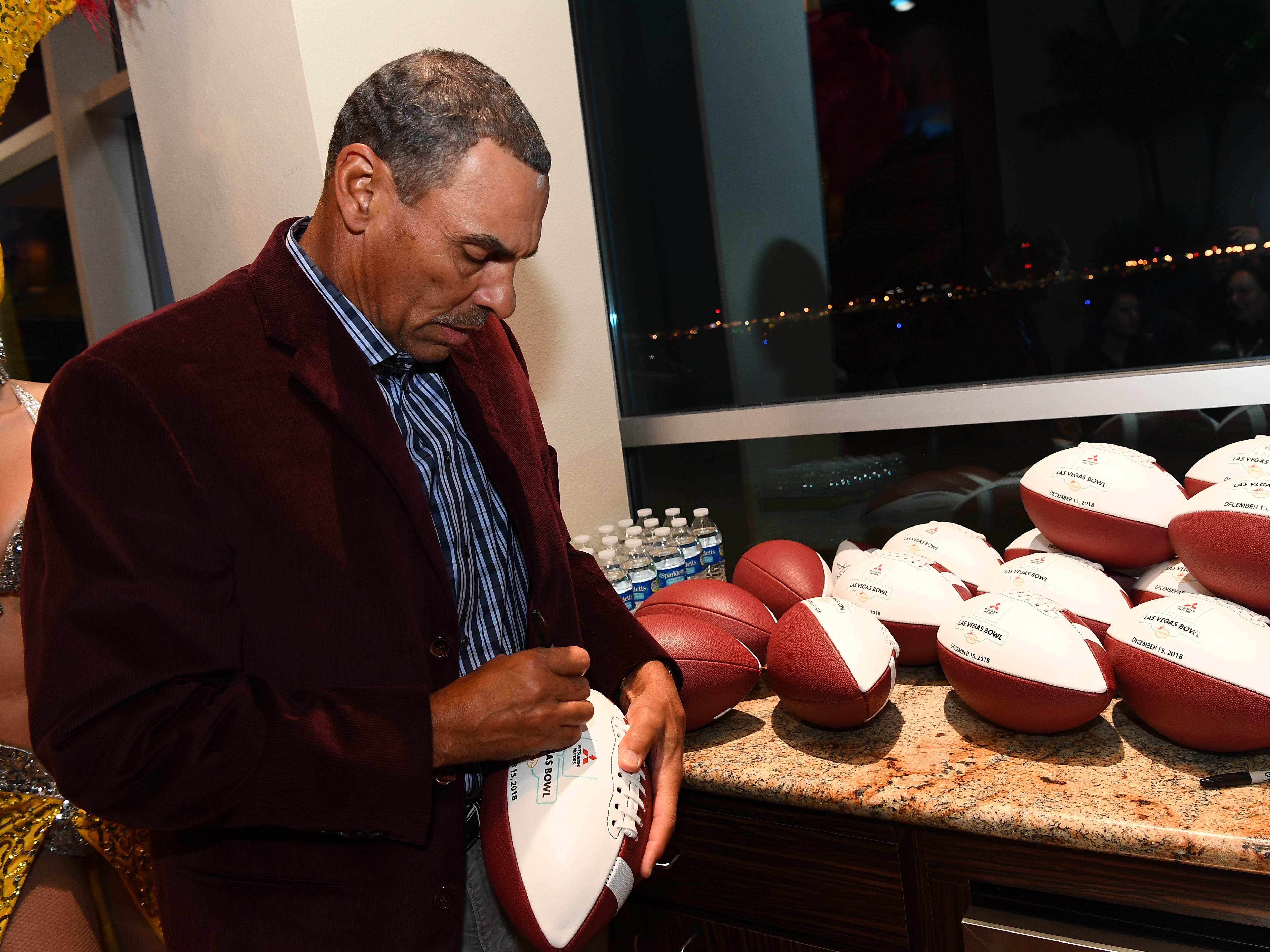 ASU head coach Herm Edwards signs footballs during a media event in Las Vegas on Tuesday.