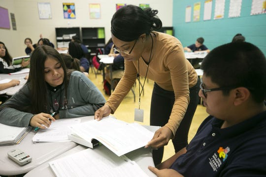 Math teacher Kori Hayles helps Angelina Parr, 12, and Raul Samano, 12, in the seventh grade math class at the NFL YET College Prep Academy, a seventh-12th grade charter school in south Phoenix, on Nov. 5, 2018.