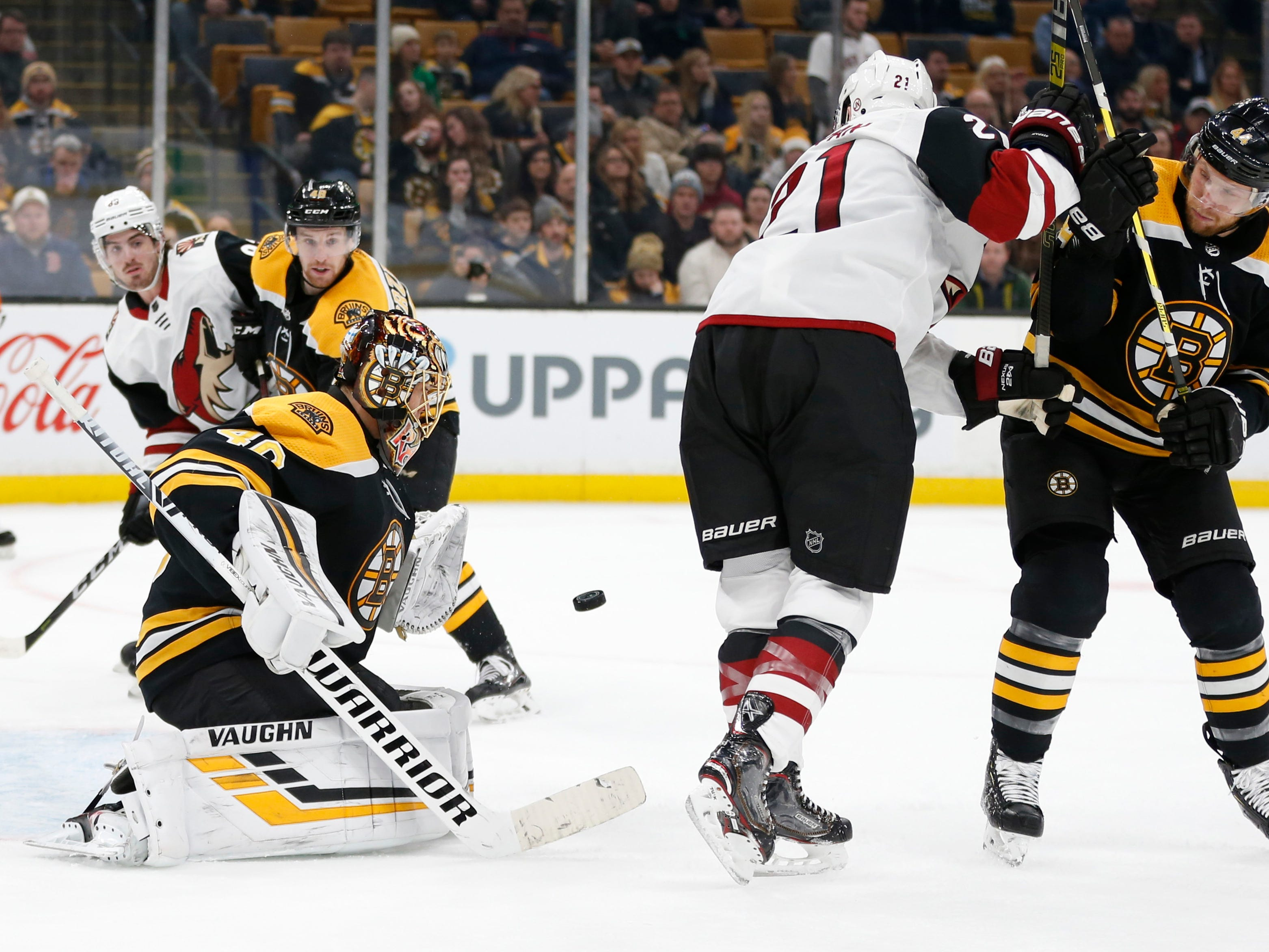 Dec 11, 2018; Boston, MA, USA; Boston Bruins goaltender Tuukka Rask (40) makes a save while defenseman Steven Kampfer (44) battles with Arizona Coyotes center Derek Stepan (21) during the third period at TD Garden. Mandatory Credit: Greg M. Cooper-USA TODAY Sports