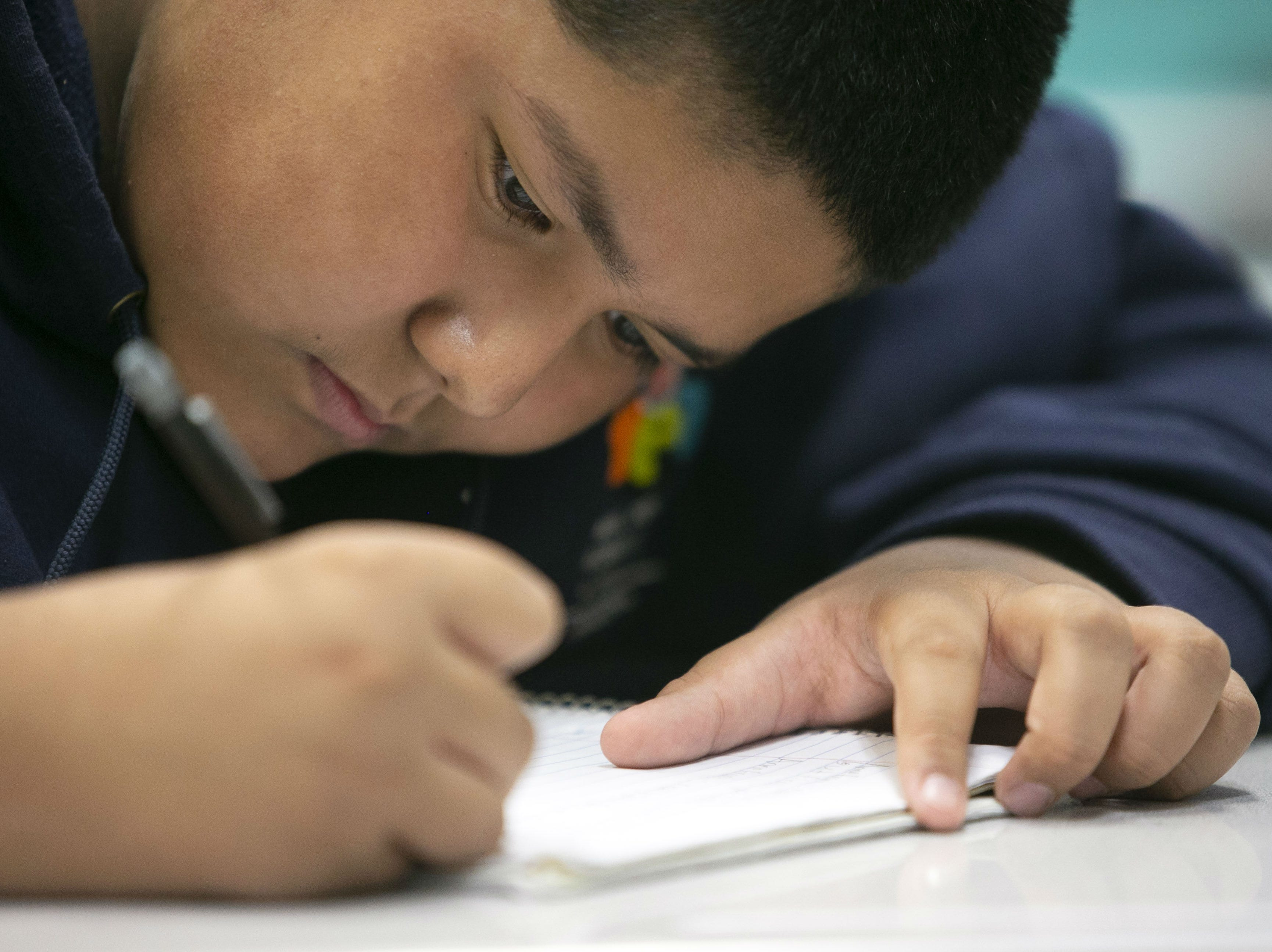Alejandro Perez, 13, works in a seventh grade literature class at the NFL YET College Prep Academy, a seventh-12th grade charter school in south Phoenix, on Nov. 5, 2018.