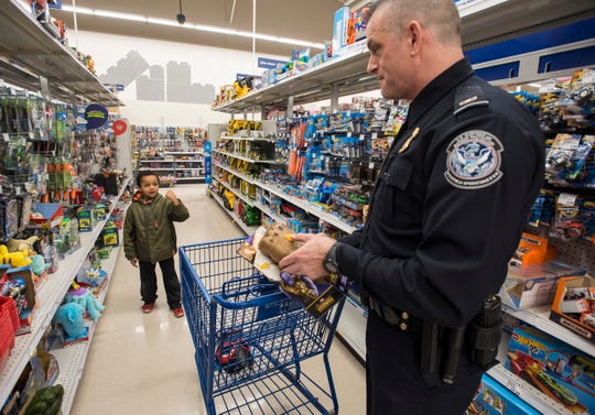 Carter Bumgardner, 7, left, describes how an Avengers toy works to U.S. Customs and Border Protection Officer Scott Graham at Christmas with a Cop Tuesday, Dec. 11, 2018 at Meijer in Fort Gratiot.