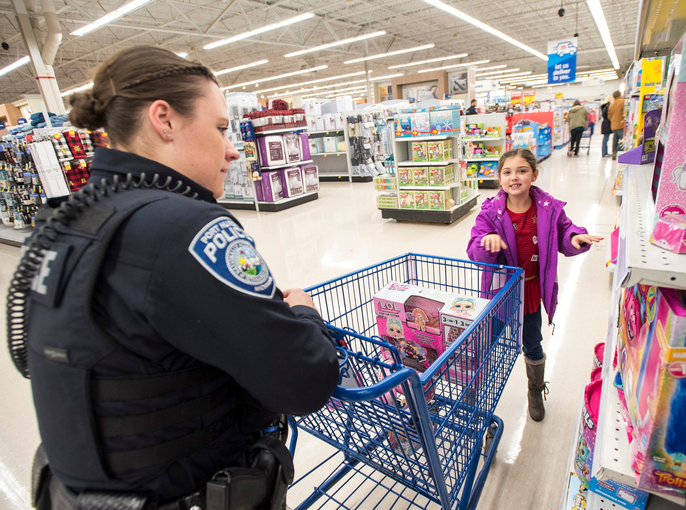 Port Huron Police Officer Sarah Cook, left, helps Tayler Hamilton, 7, shop at Christmas with a Cop Tuesday, Dec. 11, 2018 at Meijer in Fort Gratiot.