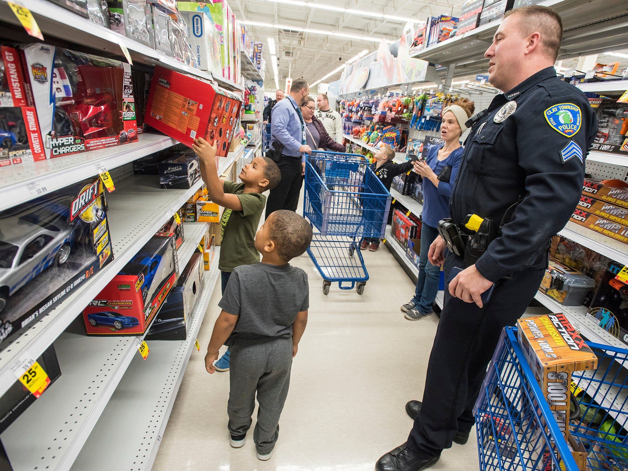 Clay Township Police Sgt. Steve Stockwell, right, watches brothers Cedrick, 6, and Dezmond Walker, 6, shop for remote controlled cars at Christmas with a Cop Tuesday, Dec. 11, 2018 at Meijer in Fort Gratiot.