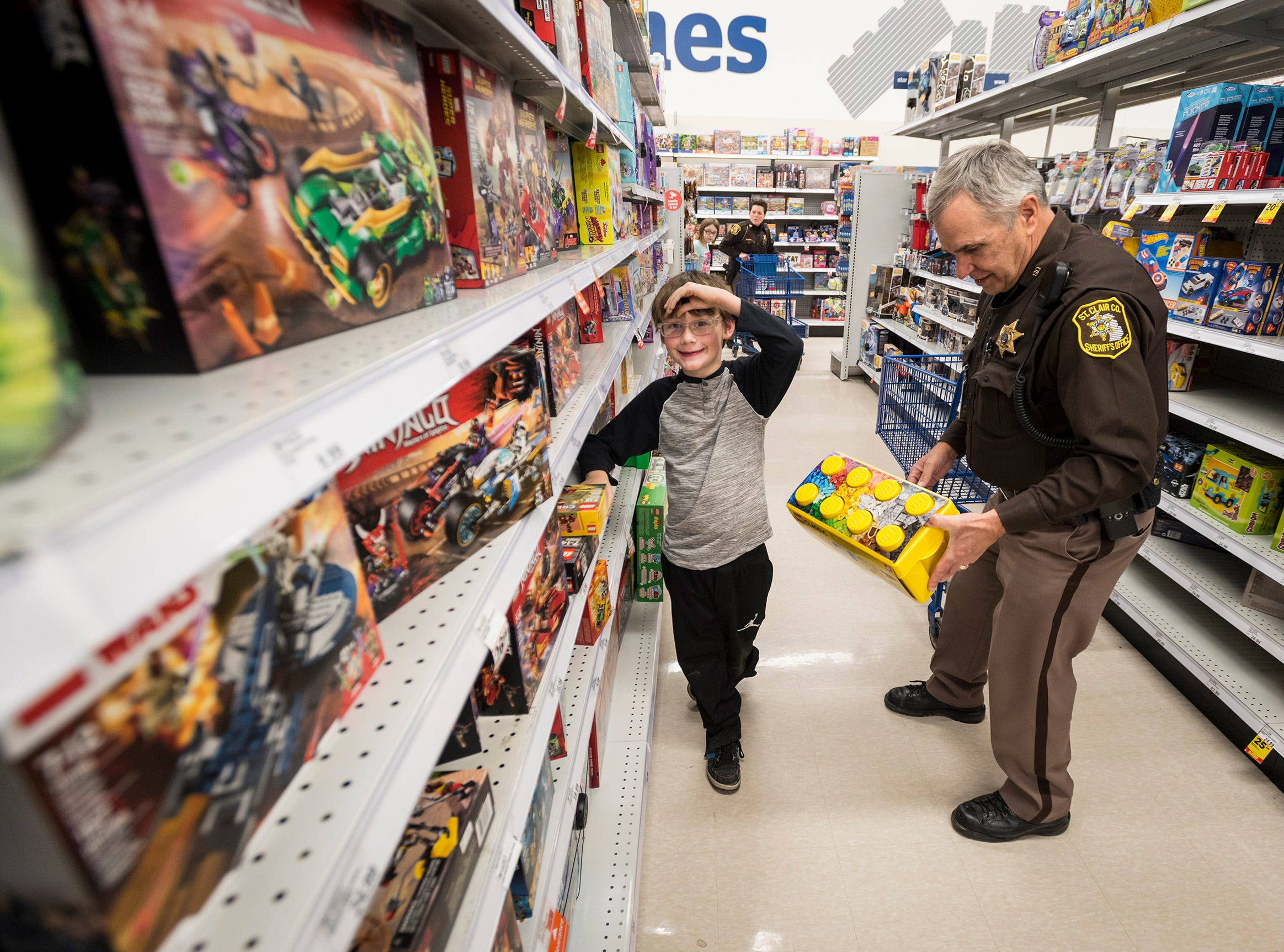 St. Clair County Deputy Richard Deshon, right, shops for Legos with Charles Leason, 8, at Christmas with a Cop Tuesday, Dec. 11, 2018 at Meijer in Fort Gratiot.