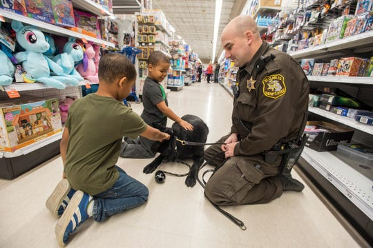 St. Clair County Sheriff Deputy Mike Pink, right,  watches Cedrick and Dezmond Walker pet Faust, a St. Clair County Sheriff's drug dog at Christmas with a Cop Tuesday, Dec. 11, 2018 at Meijer in Fort Gratiot.