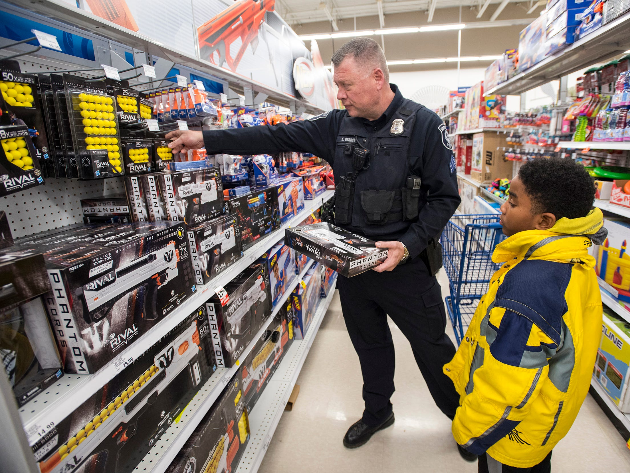 Marysville Police Sgt. Ed Gerrow, left, helps Cori'ye Hundley, 10, shop for Nerf guns at Christmas with a Cop Tuesday, Dec. 11, 2018 at Meijer in Fort Gratiot.