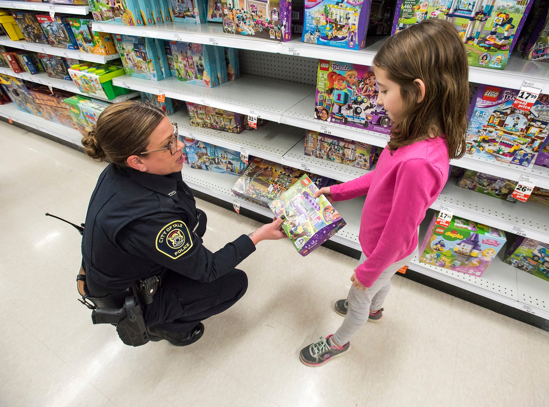 Yale Police Officer Jodi Soucy, left, shops for Legos with Kimberly Walker, 7, at Christmas with a Cop Tuesday, Dec. 11, 2018 at Meijer in Fort Gratiot.