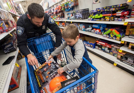 Port Huron Police Officer Dennis Huisman, right, sorts through toys with Michael Davis, 7, at Christmas with a Cop Tuesday, Dec. 11, 2018 at Meijer in Fort Gratiot.