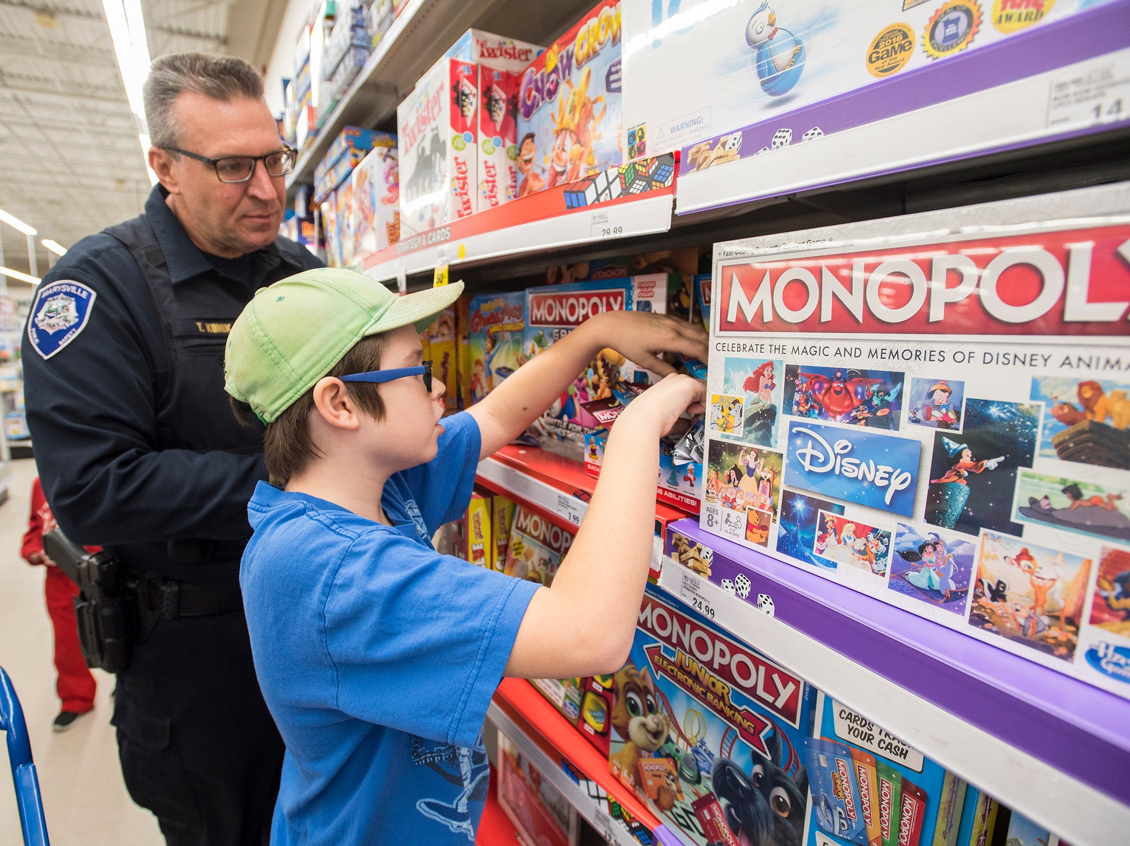 Marysville Public Safety Chief Tom Konik helps Ryan Lake, 10, shop for Monopoly pieces at Christmas with a Cop Tuesday, Dec. 11, 2018 at Meijer in Fort Gratiot.
