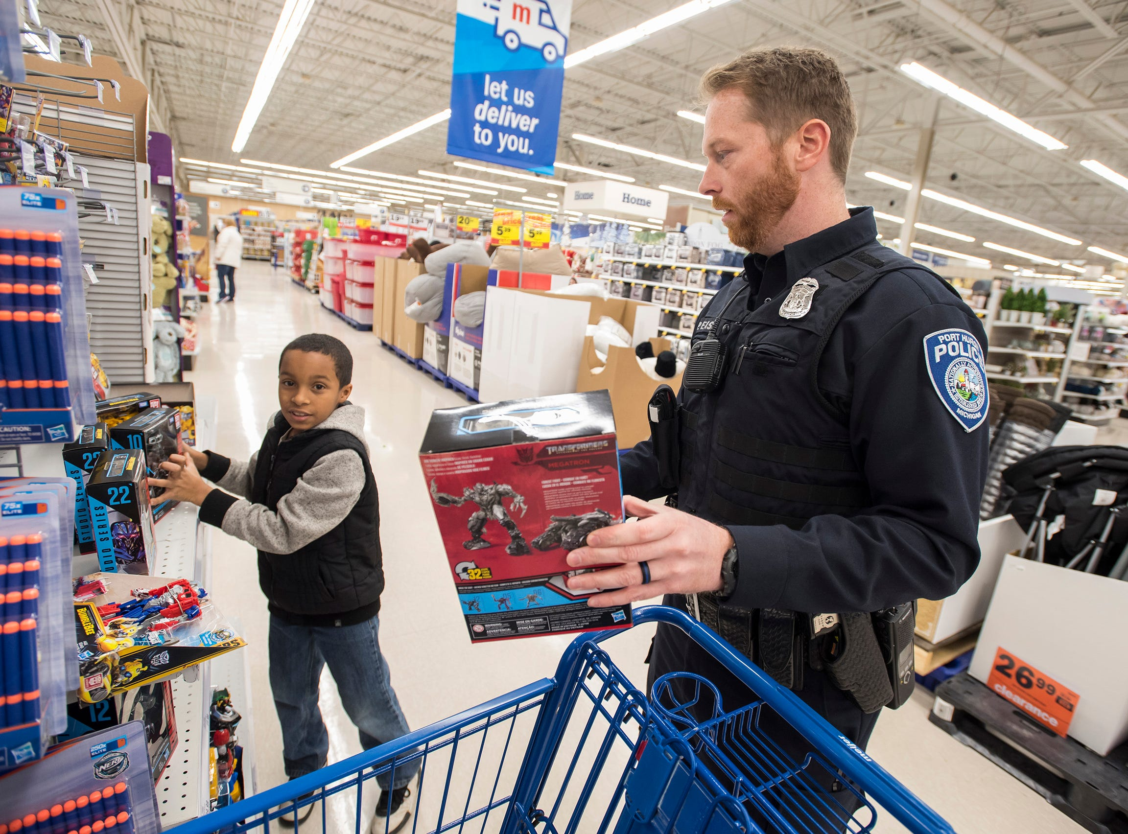 Port Huron Police Officer Pat Eash, right, helps Dominic Kunia, 11, pick out Transformers toys at Christmas with a Cop Tuesday, Dec. 11, 2018 at Meijer in Fort Gratiot.