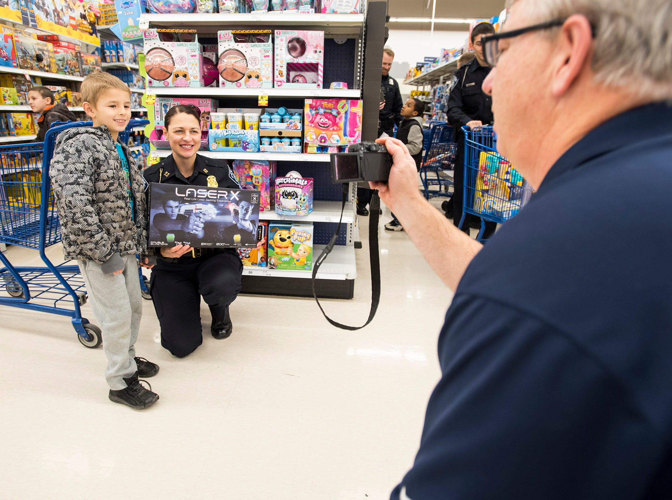 St. Clair County Sheriff Public Information Officer Steve Campau, right, takes a photo of Port Huron Police Capt. Marcy Kuehn, center, and Adrian Villarreal, 8, at Christmas with a Cop Tuesday, Dec. 11, 2018 at Meijer in Fort Gratiot.