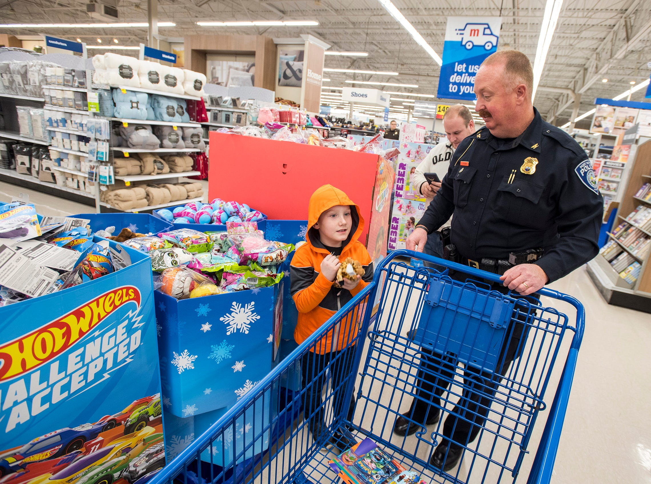 Port Huron Police Chief Joseph Platzer, right, helps Kaleb Chuhran, 6, shop for stuffed animals at Christmas with a Cop Tuesday, Dec. 11, 2018 at Meijer in Fort Gratiot.