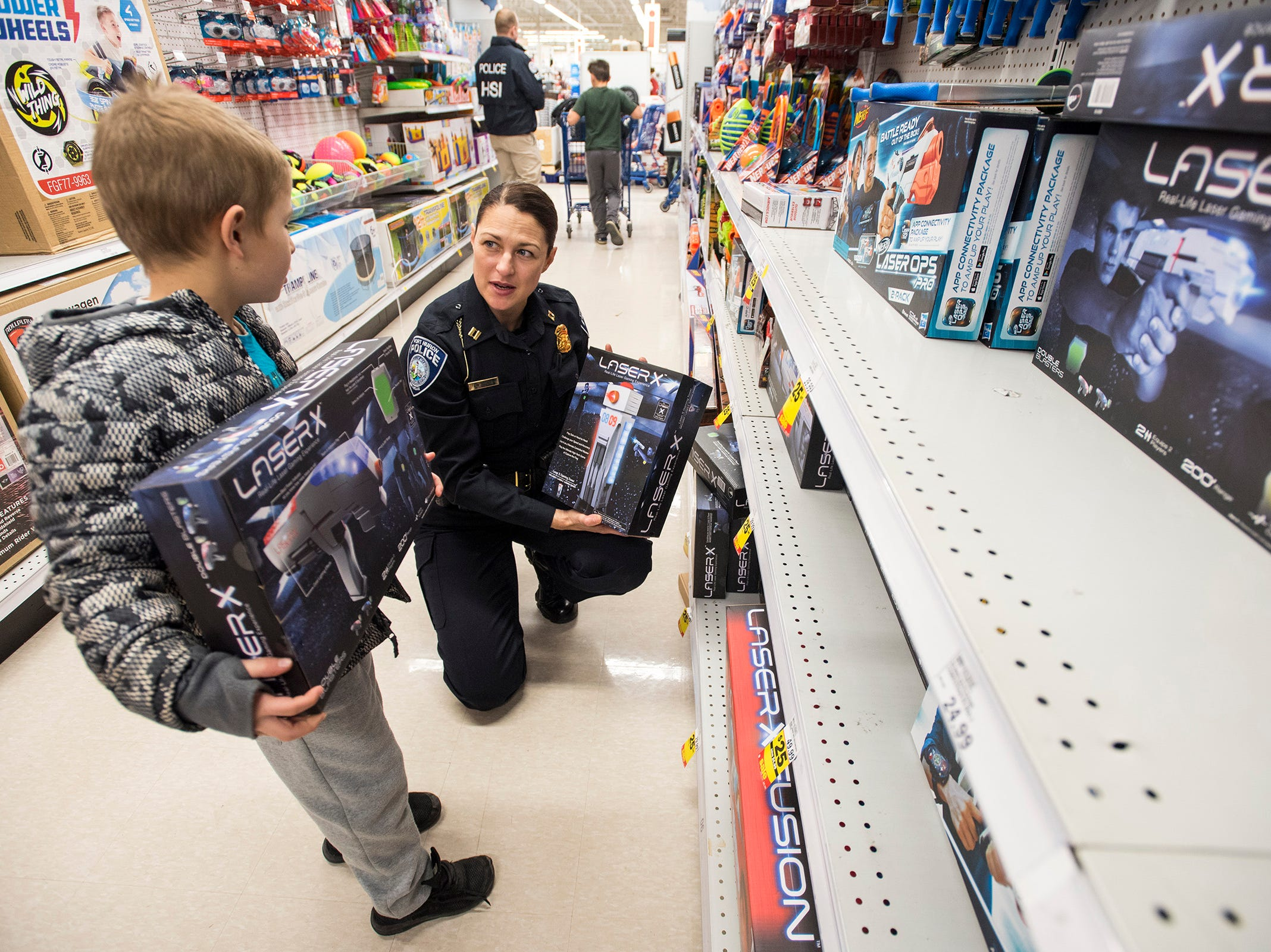 Port Huron Police Capt. Marcy Kuehn, right, helps Adrian Villarreal, 8, shop for a laser gun game at Christmas with a Cop Tuesday, Dec. 11, 2018 at Meijer in Fort Gratiot.
