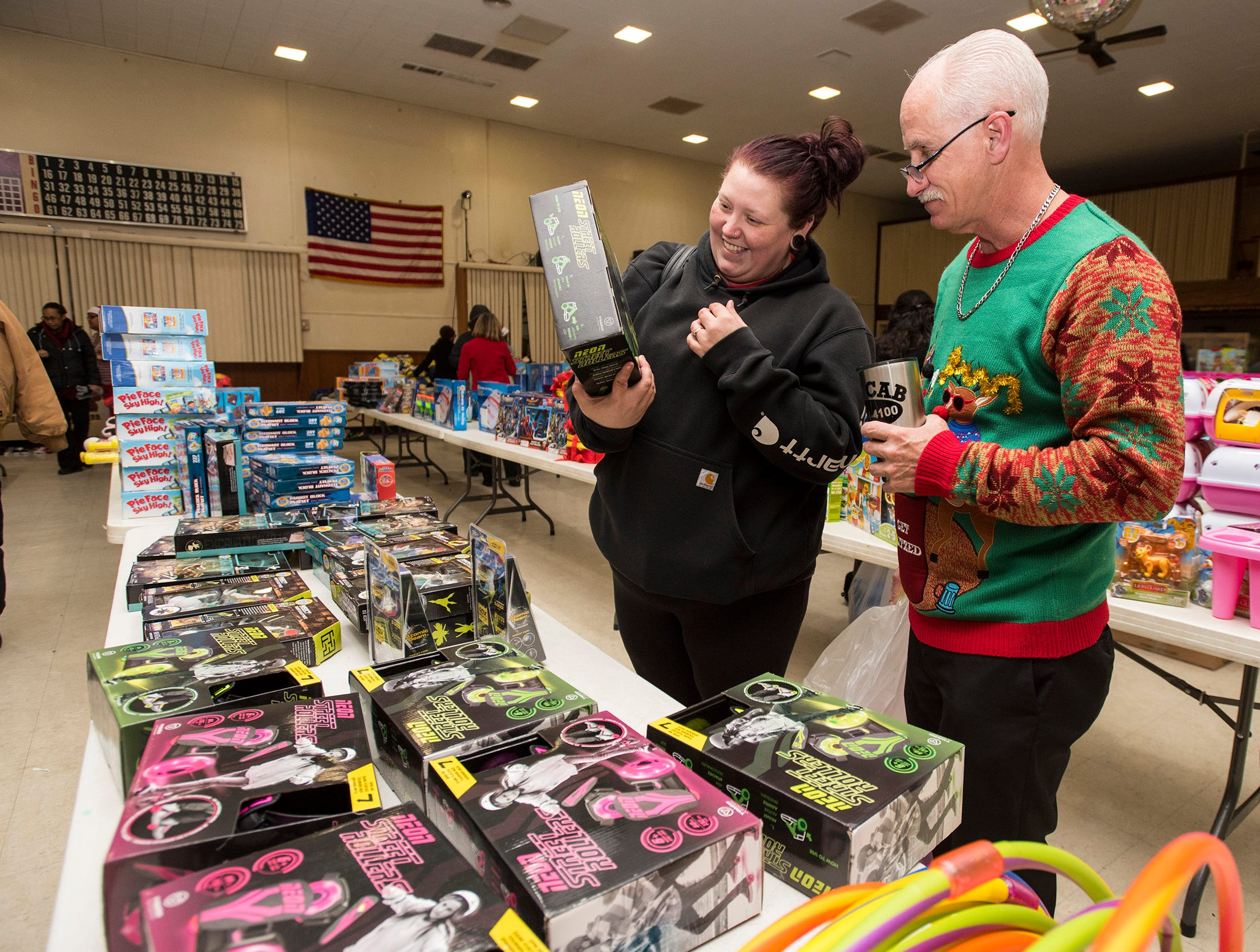 Volunteer Dennis Cooper, right, helps Alicia Patterson find toys for her 10-year-old son and 2-year-ld daughter Wednesday, Dec. 12, 2018 during the annual toy giveaway at the Charles Hammond American Legion Post in Port Huron.