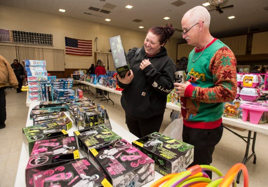 Volunteer Dennis Cooper, right, helps Alicia Patterson find toys for her 10-year-old son and 2-year-old daughter at the Toys for Kids giveaway in this 2018 file photo.
