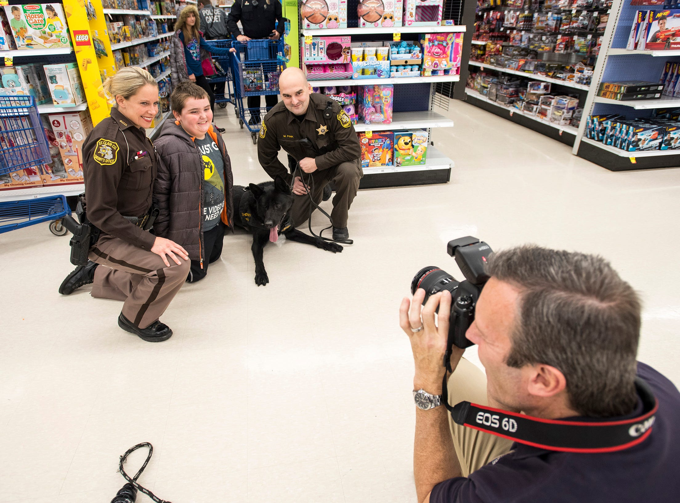 St. Clair County Sheriff Detective Kelsey Wade, left, and Wyatt Klimowicz pose for a photo with Deputy Mike Pink, right, and his drug dog Faust at Christmas with a Cop Tuesday, Dec. 11, 2018 at Meijer in Fort Gratiot.