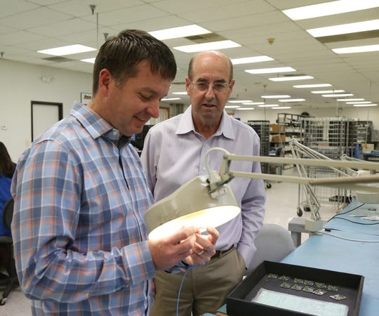 From left, general manager Tim McMorris and company founder Mike Ratliff inspect a freshly soldered set of PCBs at Marco Manufacturing in the Town of Poughkeepsie on December 12, 2018.
