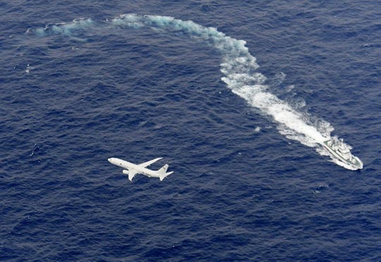 In this Dec. 6, 2018, file photo, Japan's Coast Guard ship, top, and U.S. military plane are seen at sea off Kochi, southwestern Japan, during a search and rescue operation for missing crew members of a U.S. Marine refueling plane and fighter jet. The U.S. Marine Corps have declared that five crewmembers dead after their aircraft crashed last week off Japan's southern coast and that their search has ended.