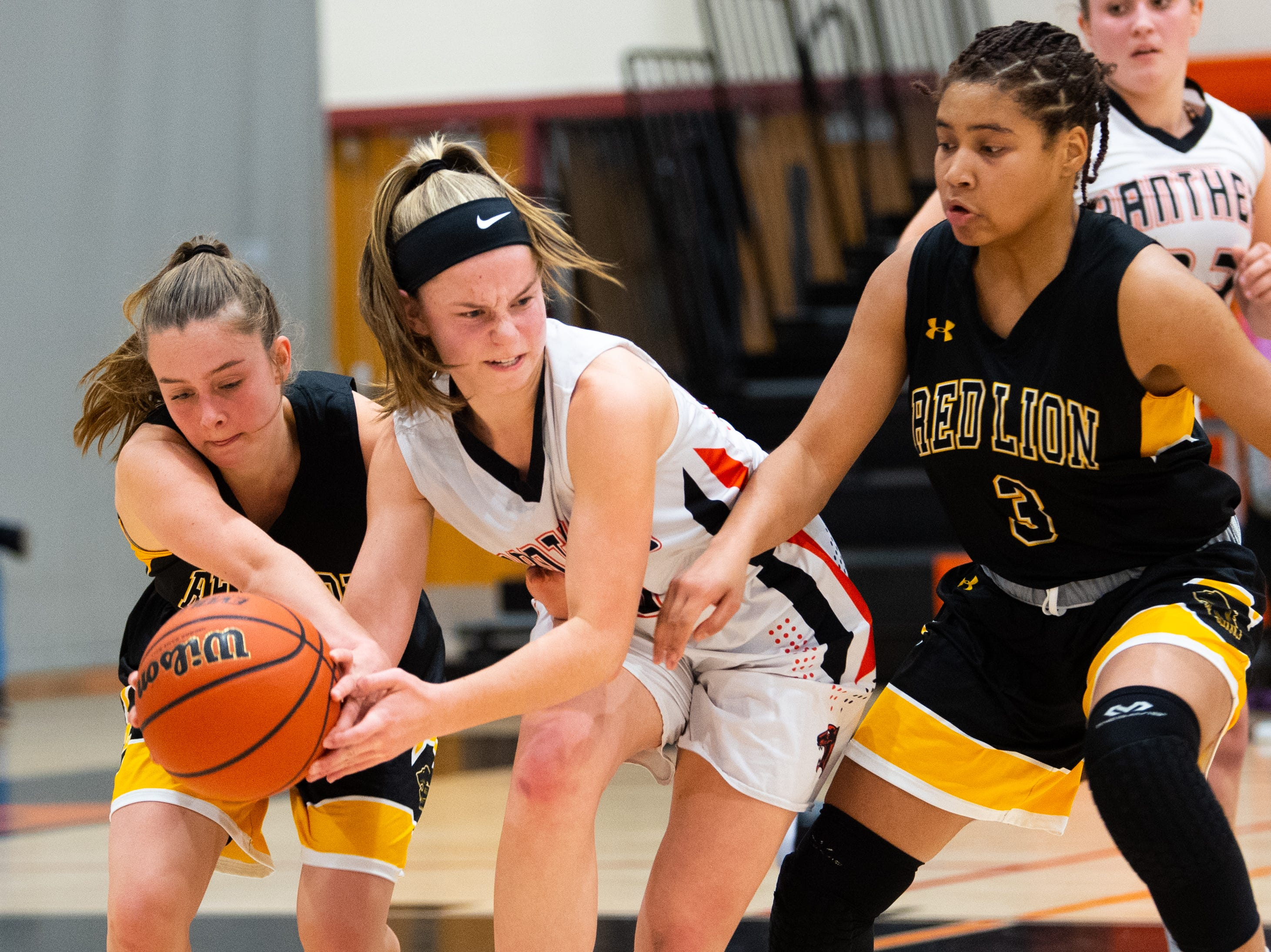 Alleney Klunk (10) and Asia Eames (3) of Red Lion try to steal the ball from Sarah Berman (23) of Central York during the girls' basketball game, Tuesday, December 11, 2018. The Panthers defeated the Lions 40-38.