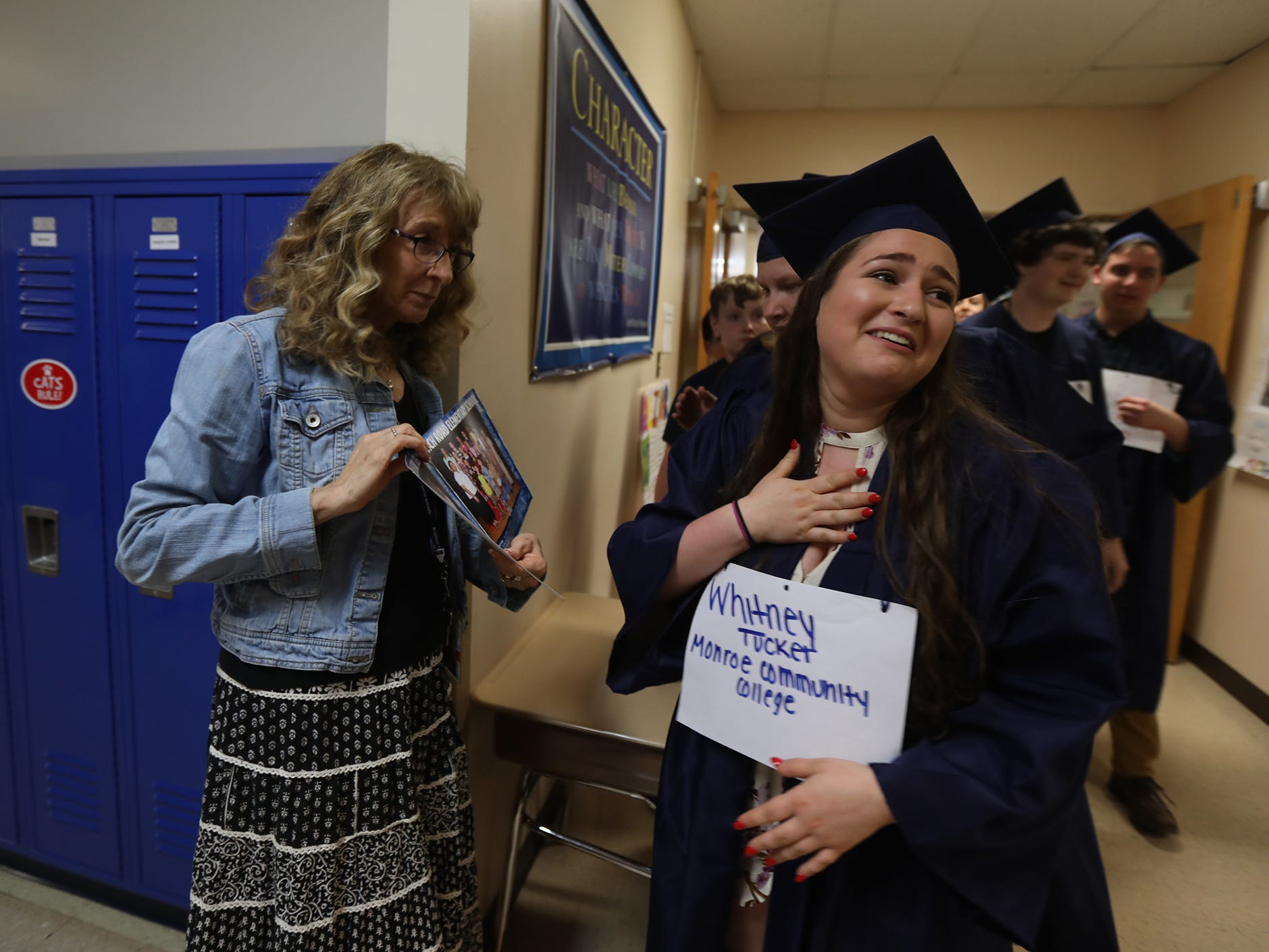 Whitney Tucket reacts after seeing her fourth grade photo.  Ina Sham, fourth grade teacher, showed the photo to  graduating seniors to see as they paraded by on June 11, 2018.
