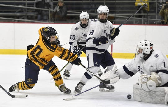 Spencerport's AJ Giannavola, left, puts the game-winner past Gates Chili goalie Charles Healey during a regular season game played at Genesee Valley Ice Arena, Tuesday, Dec. 11, 2018.