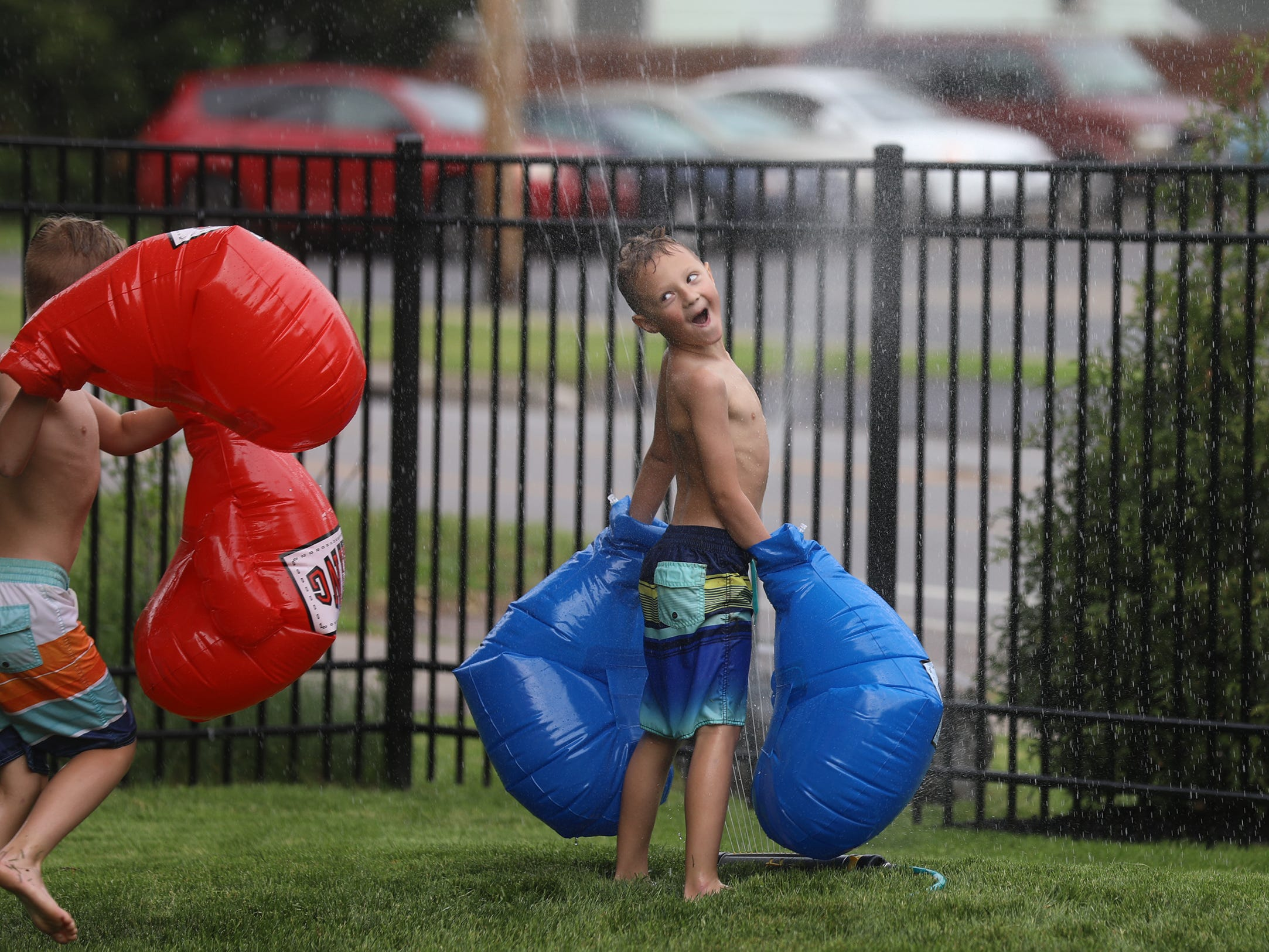 Levi René, 6, cools off in the sprinkler and reacts as his brother, Finn, 8,  comes running at him to continue their inflatable boxing game. The brothers were playing in their yard on St. Paul Boulevard, Irondequoit N.Y. on this warm humid afternoon of May 26, 2018.